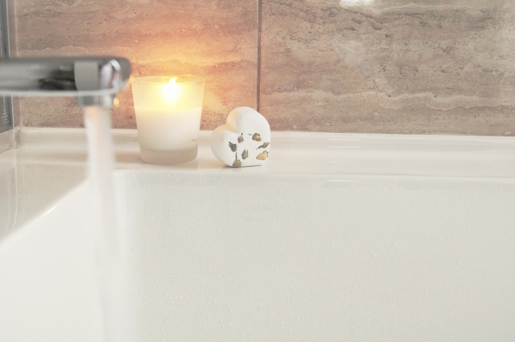 Spa night bath tub with running water and candle