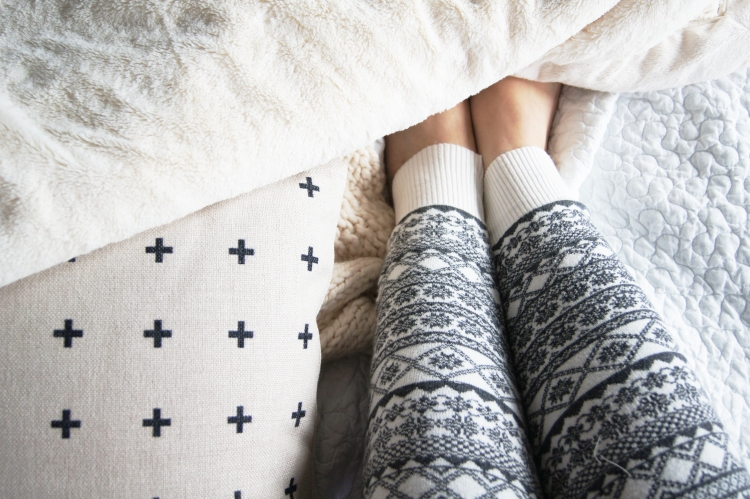 women's legs on bed in pyjamas ready for bed