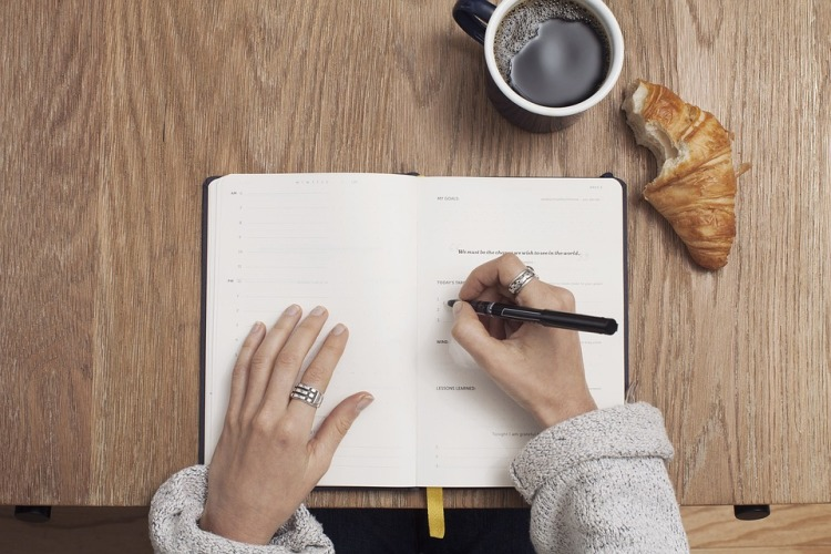 writing goals in journal with coffee and croissant