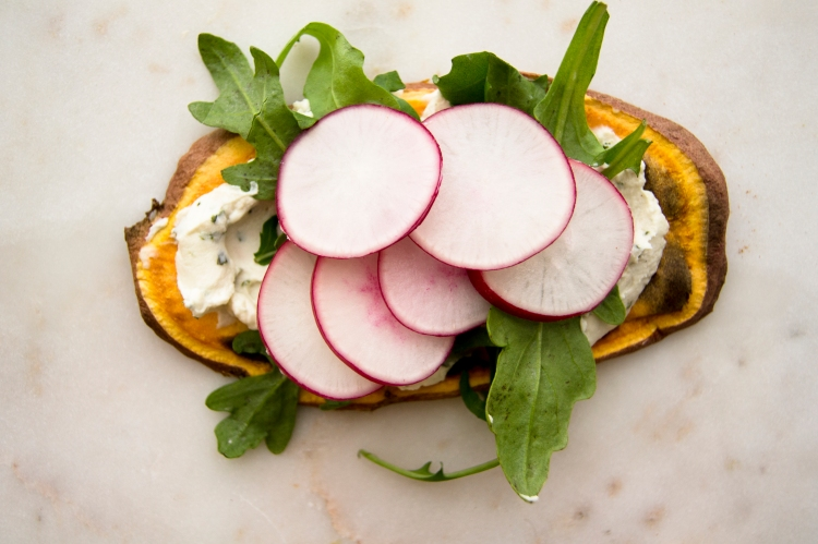 sweet potato toast topped with cream cheese, arugula greens and sliced radish toppings