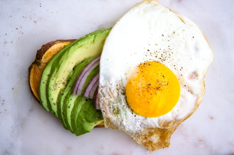 sweet potato toast with avocado, red onion, and egg toppings