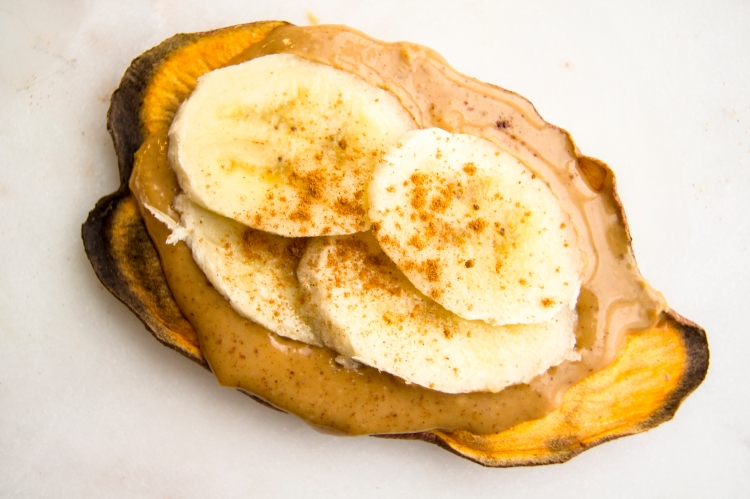 sweet potato toast topped with peanut butter almond butter, banana and cinnamon toppings